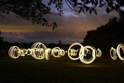 Multiple circles of light formed by people waving lights