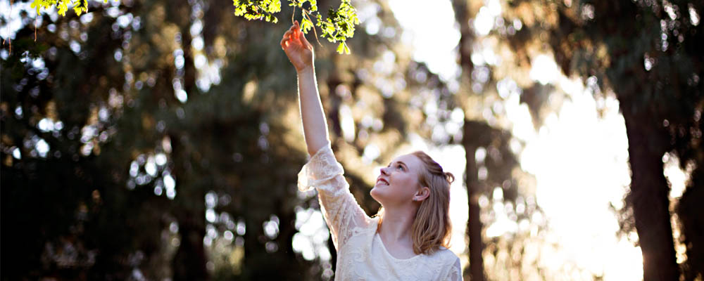 Portrait of a girl reaching for a tree branch above her