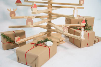 A wooden christmas tree with gifts at its base